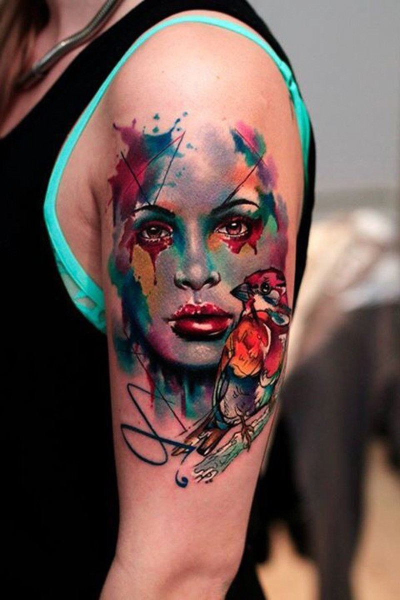 Abstract style colored woman portrait tattoo on shoulder combined with little bird
