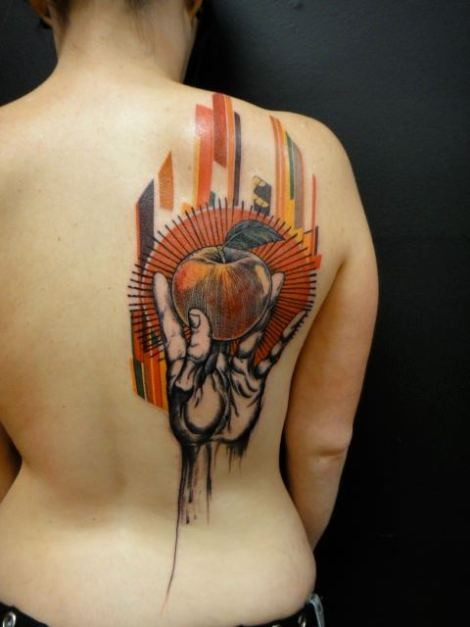 Abstract style colorful hand with apple on upper back tattoo