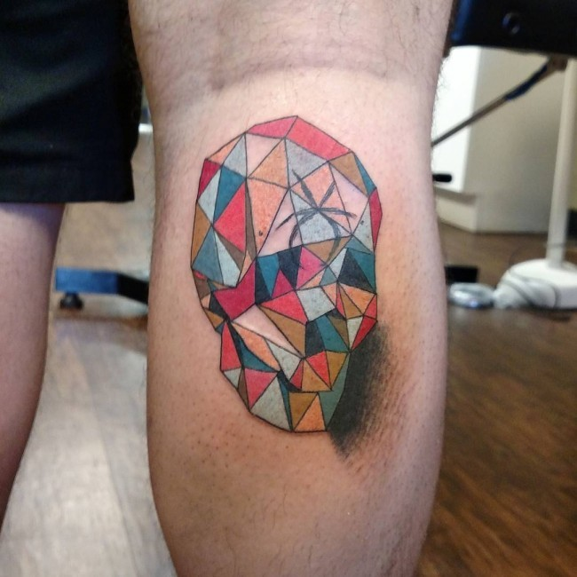Abstract style multicolored face shaped tattoo on leg