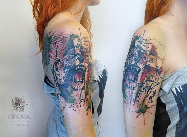 Abstract style multicolored lion face tattoo on shoulder with various ornaments