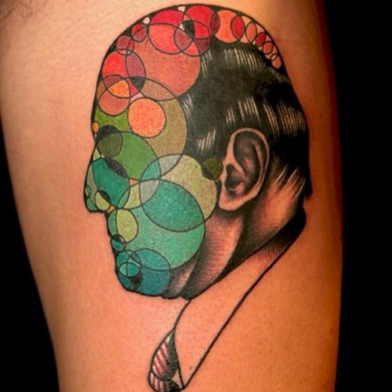 astratto stile dipinto meta faccia uomo meta cerchie colorati tatuaggio su braccio