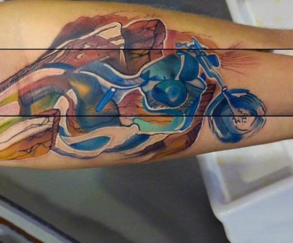 Abstract style watercolor like little bike tattoo on arm