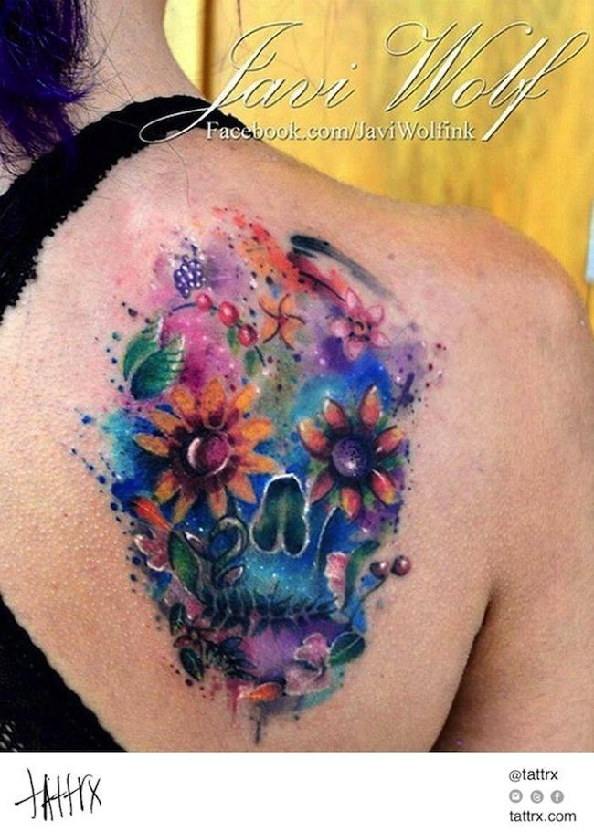 Abstract style watercolor like shoulder tattoo of mystical skull stylized with flowers