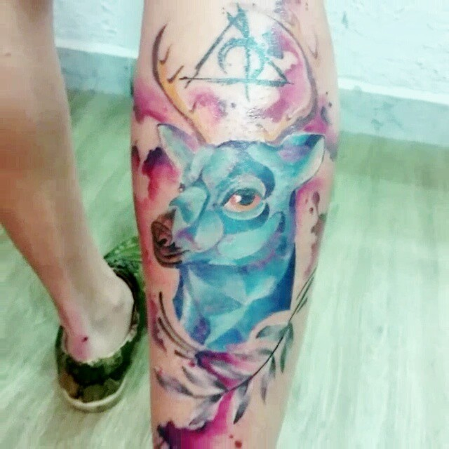 Abstract styli watercolor like little deer tattoo on leg stylized with mystical symbol and leaf