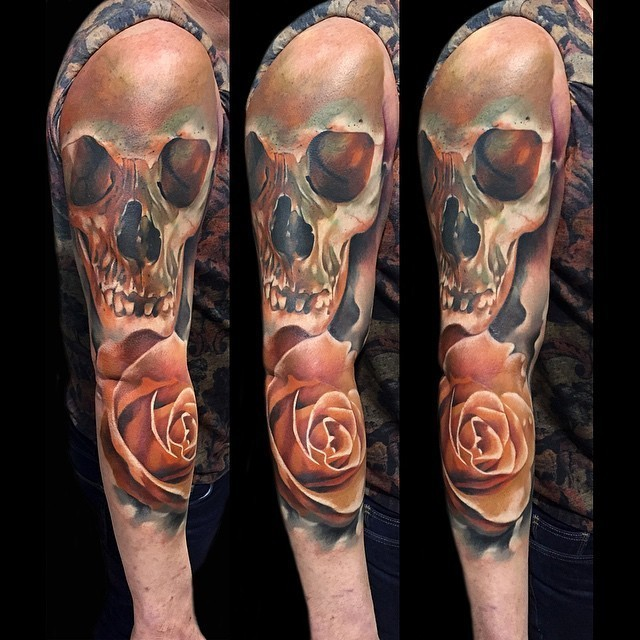 Accurate lifelike colored human skull tattoo on sleeve with realistic rose