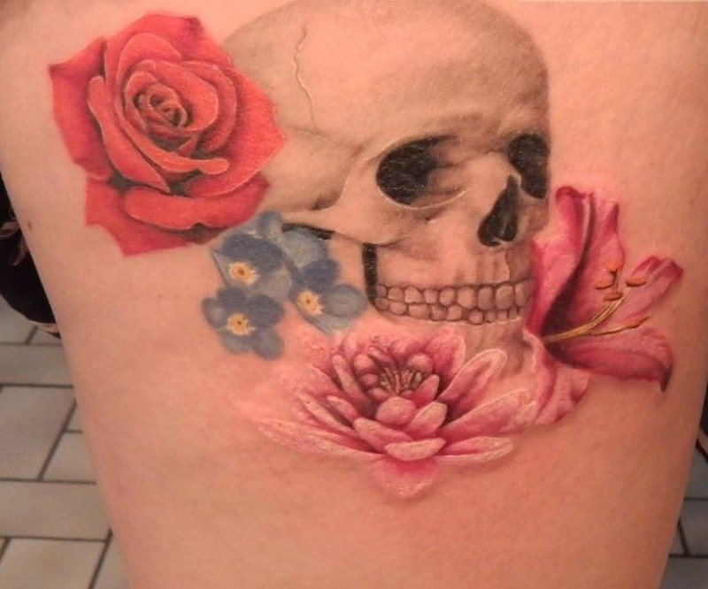 Accurate pained and colored human skull tattoo on thigh with various multicolored flowers