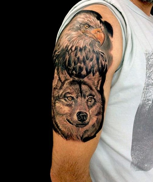 Accurate painted and colored very detailed eagle and wolf tattoo on upper arm