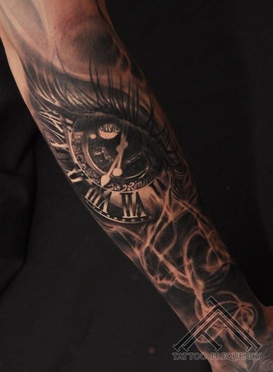 Tatuaje en el antebrazo, ojo con reloj en él, estilo precioso