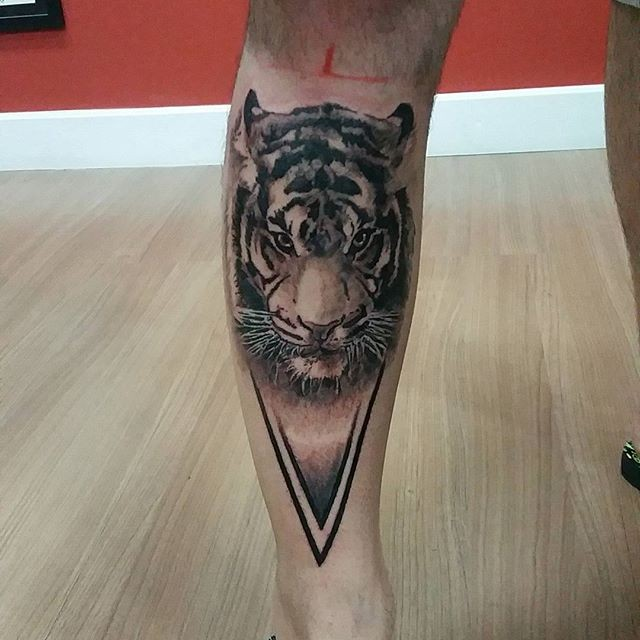 Accurate painted black ink leg tattoo of tiger head with triangle part