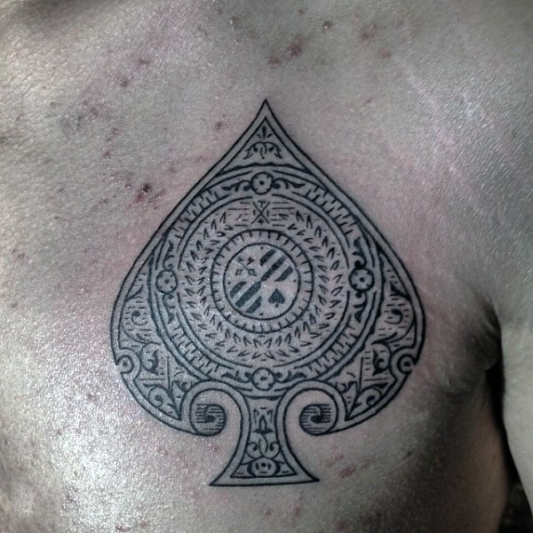 Accurate painted little black ink spades symbol stylized with beautiful ornaments tattoo on chest