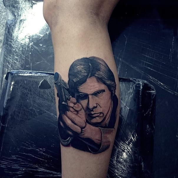Accurate very detailed colored Han Solo portrait with pistol tattoo on leg zone