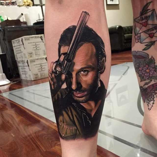 Accurate very detailed man with gun portrait tattoo on leg