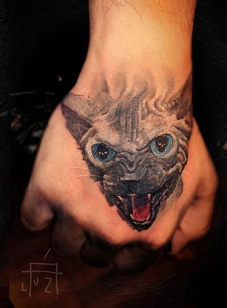 Aggressive black cat tattoo on hand