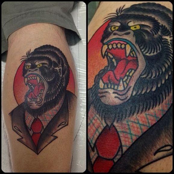 Tatuaggio colorato sulla gamba la testa di gorilla con la bocca spalancata