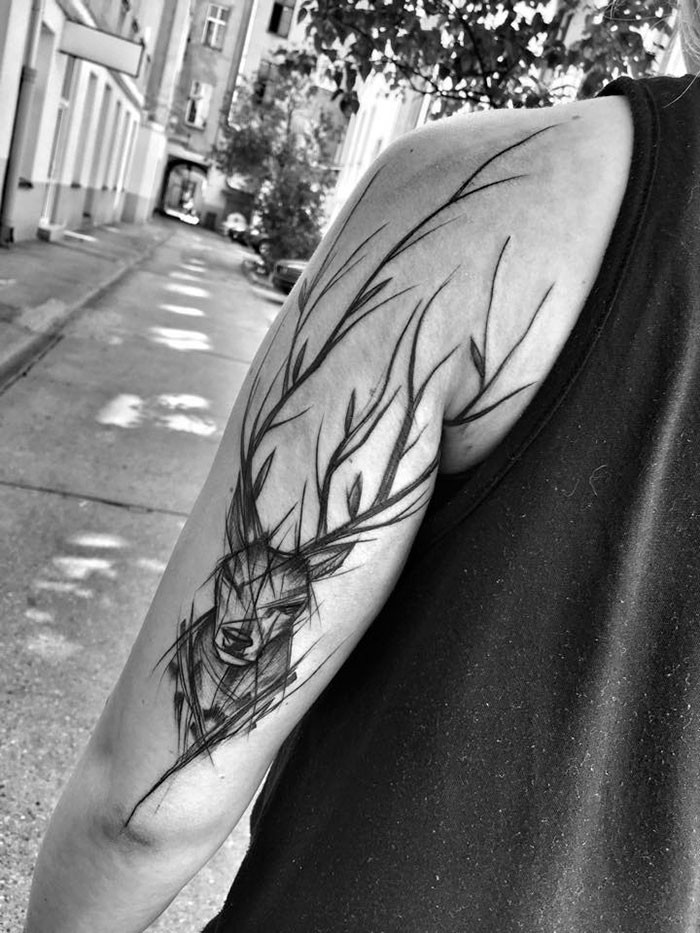Amazing black ink painted by Inez Janiak upper arm tattoo of deer with large horns