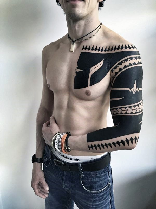 Amazing black ink tribal ornament tattoo on sleeve and chest