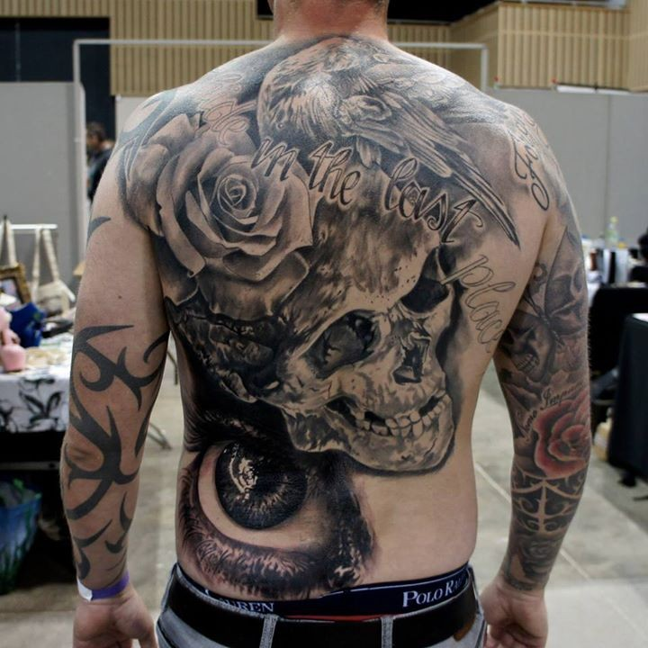Amazing detailed black ink human skull tattoo on back with eagle, lettering and flower