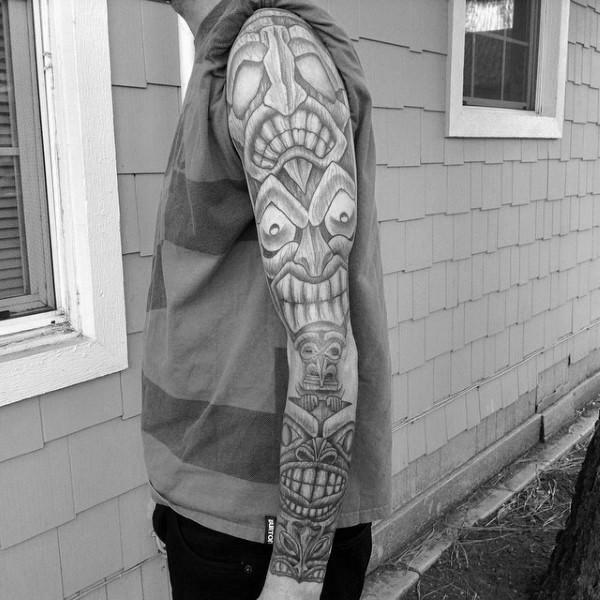 Amazing detailed creepy tribal Gods tattoo on sleeve