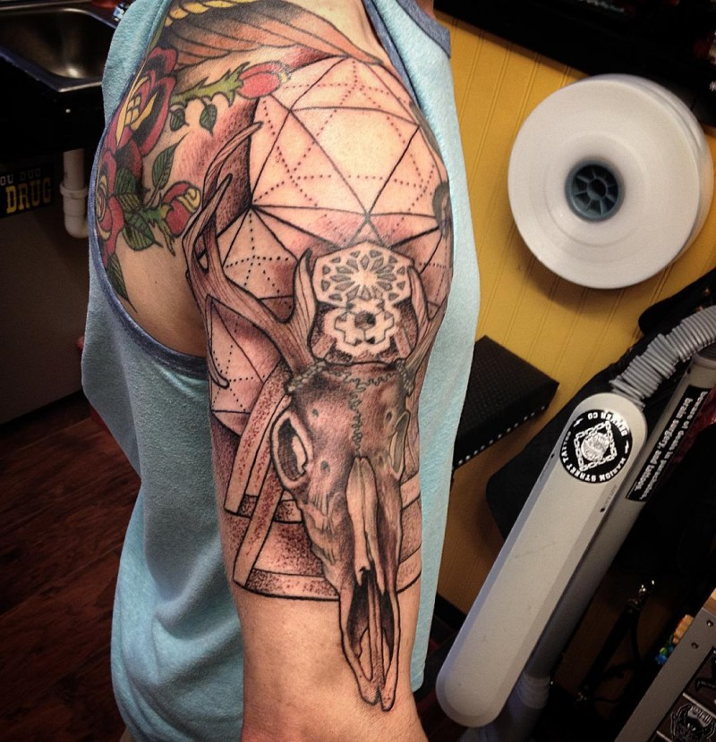 Amazing looking black ink deer skull tattoo on shoulder combined with geometrical figures