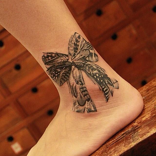 Tatuaje en el tobillo,  lazo gris grande