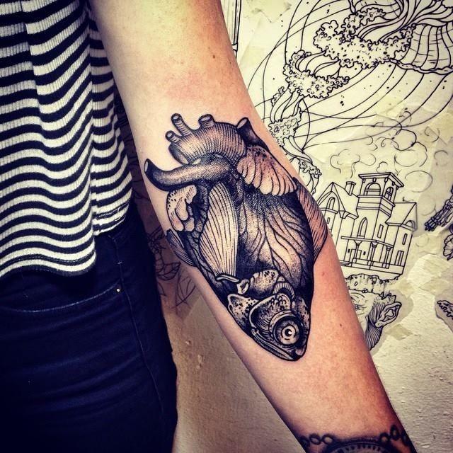 Amazing womens gray half heart-half fish tattoo on forearm