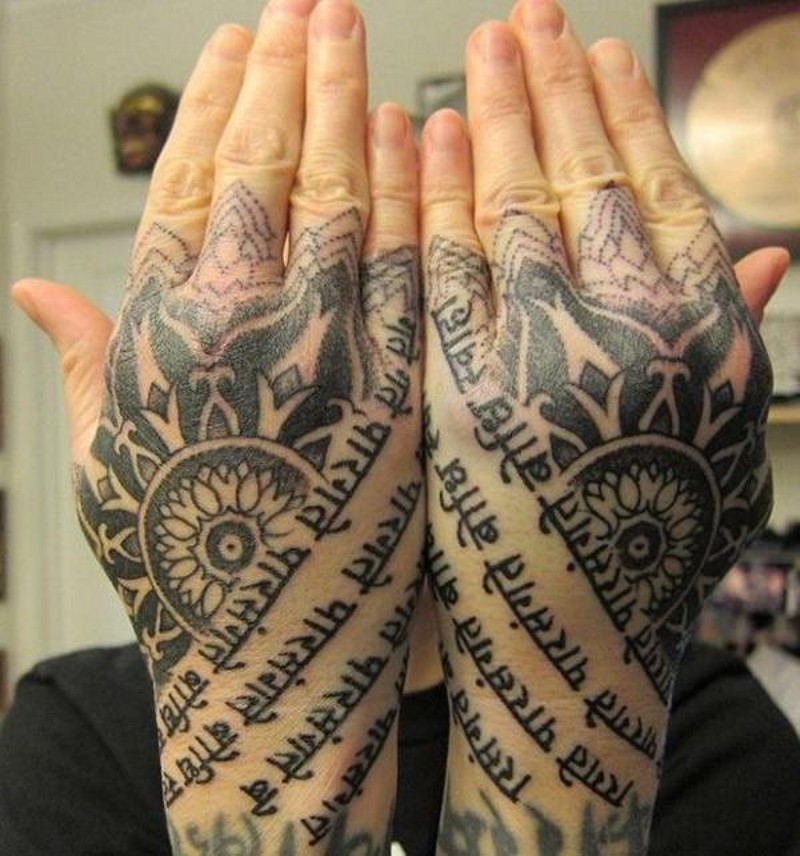 Ancient black ink lettering tattoo on hands stylized with ornamental flowers