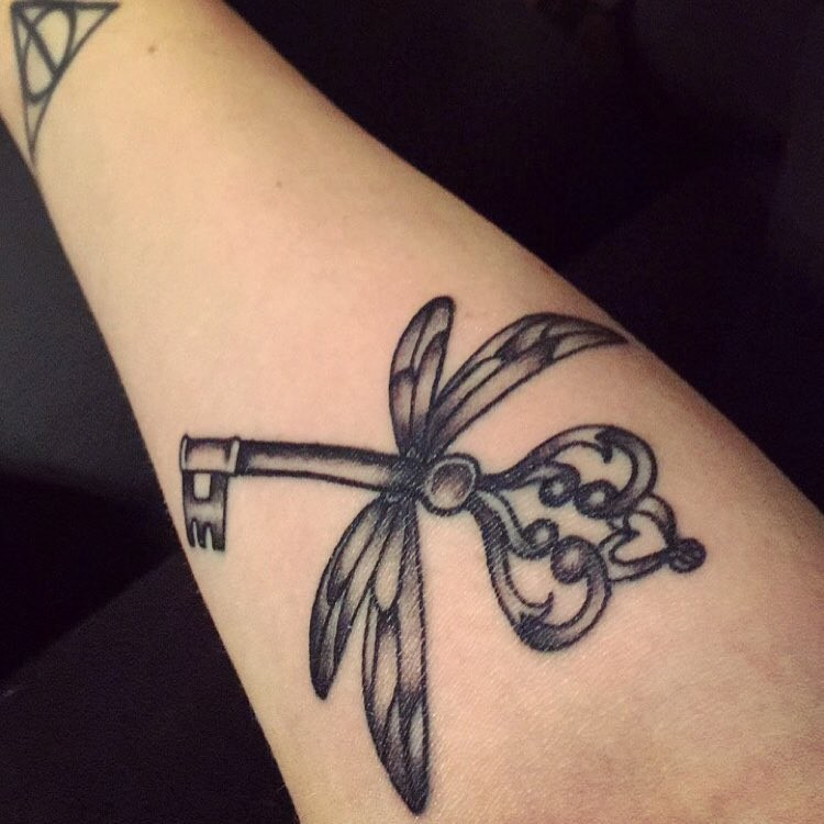 Ancient detailed key with dragonflies wings tattoo on forearm