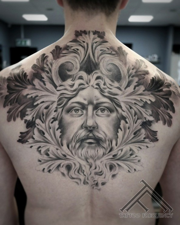 Ancient like black ink detailed back tattoo of ancient man portrait with leaves