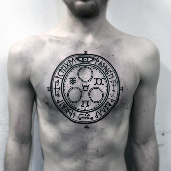 Ancient style black ink chest tattoo of circle shaped ornament with lettering and symbols