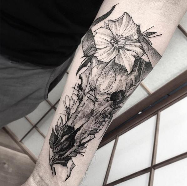 Animal horned skull with flowers forearm length dark colored tattoo in engraving style