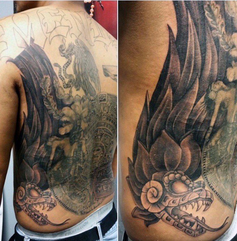 Antic style black and white tribal snake with Mayan tablet tattoo on back with unfinished lettering