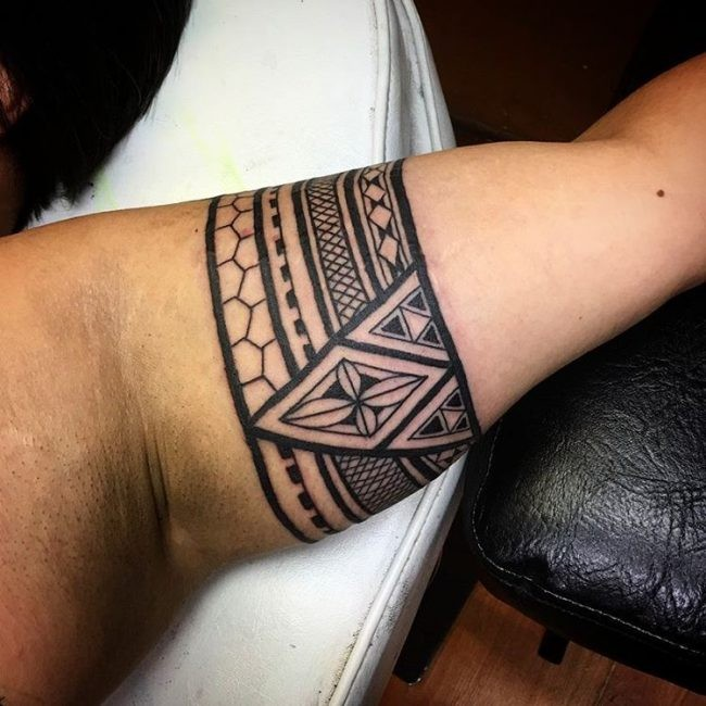 Arm band shaped black ink biceps tattoo of geometrical ornament