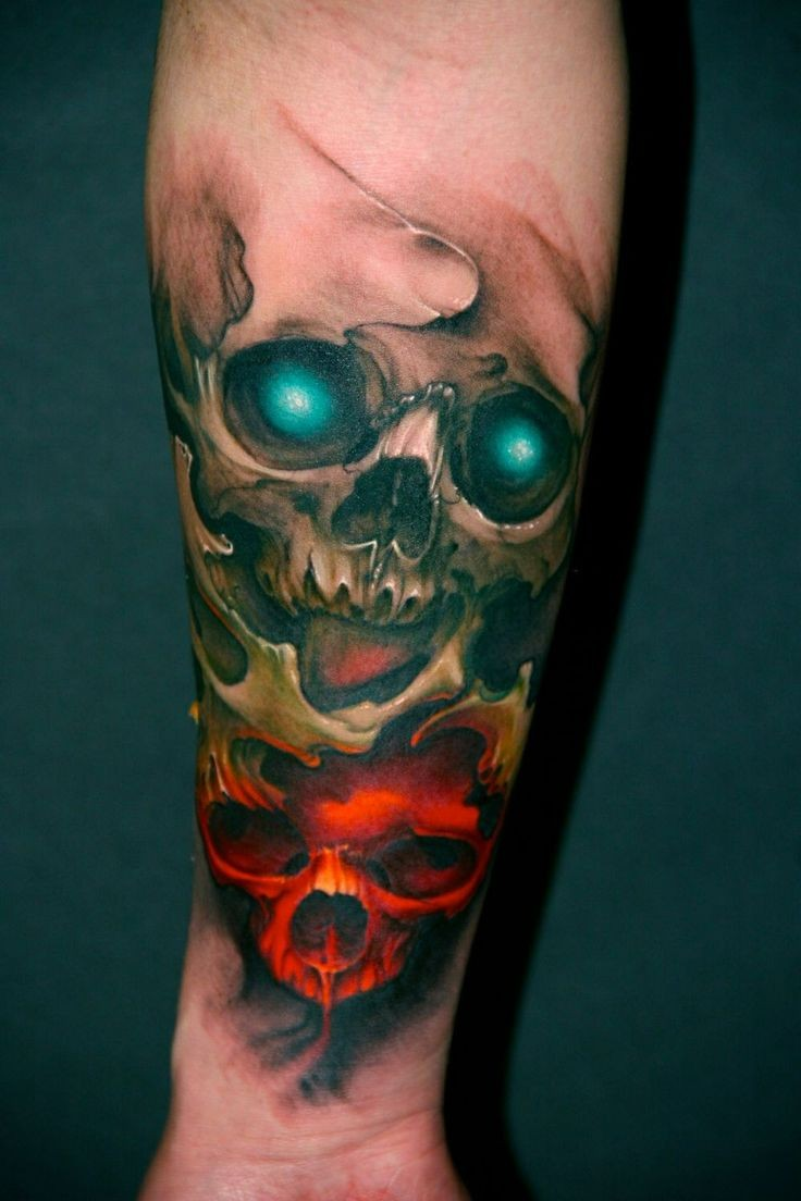 Art style colored forearm tattoo of demonic skulls with glowing eyes