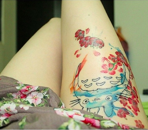 Asian cartoon colored hero tattoo on thigh stylized with red flowers