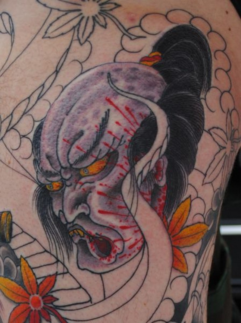 Asian native colored back tattoo of severed demons head