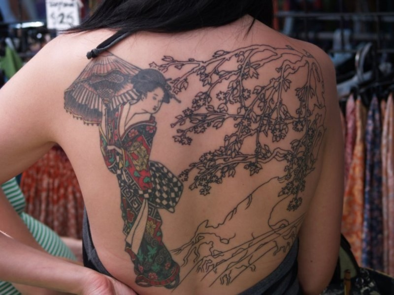 Asian native half colored whole back tattoo of nice looking geisha with blooming tree