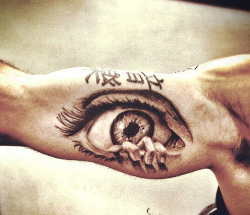 stile asiatico grande nero e bianco occhio con scrittotatuaggio su braccio