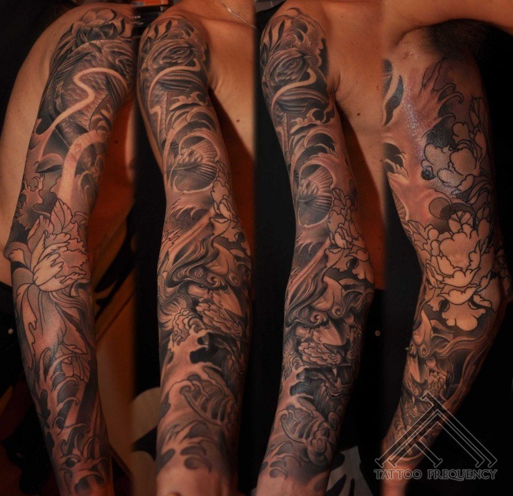 Asian style big black and white mystical dragon with flowers tattoo on arm