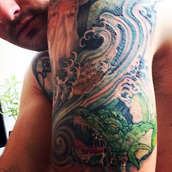 Asian style big multicolored dragon in waves arm tattoo