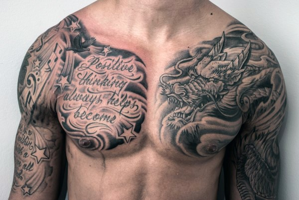 Asian style black and white dragon with lettering tattoo on chest