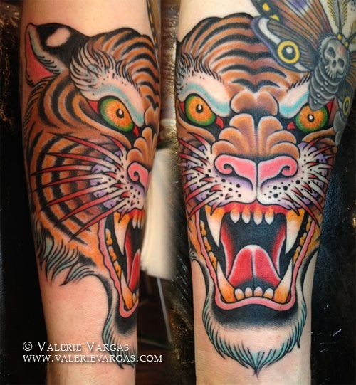 Asian style cartoon style colored roaring tiger tattoo on forearm combined with night butterfly