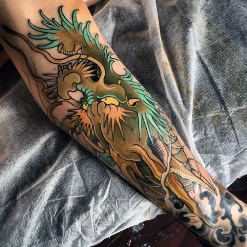 Asian style colored forearm tattoo of colored dragon head