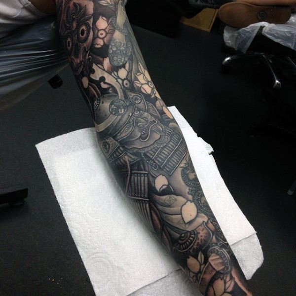 Asian style funny looking detailed sleeve tattoo of samurai warrior with various flowers