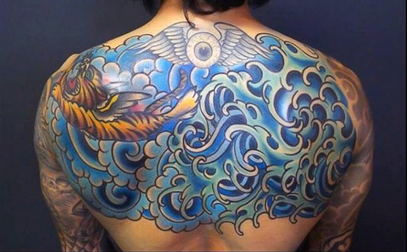 Asian style multicolored tiger in waves tattoo on upper back