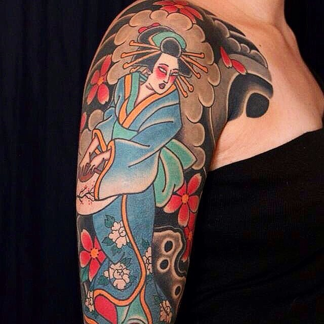 Asian style painted and colored shoulder tattoo of dancing geisha with flowers
