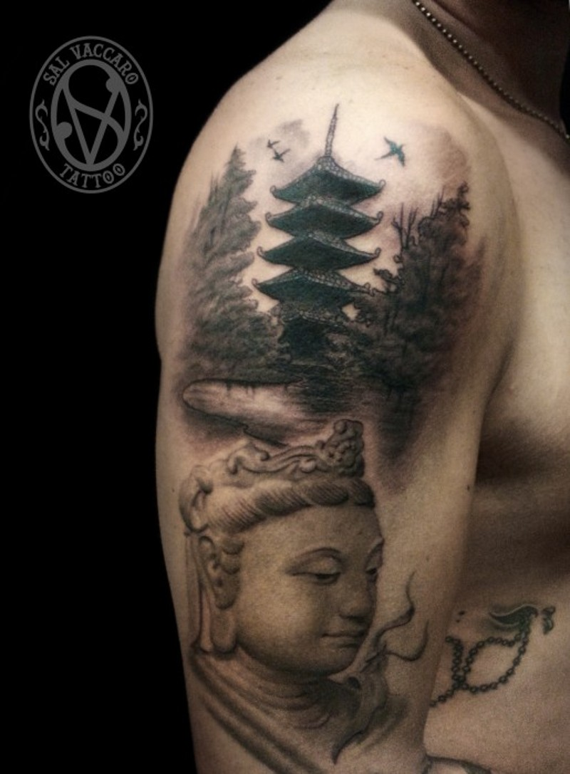 Asian themed black and white shoulder tattoo of Buddha statue and old temple