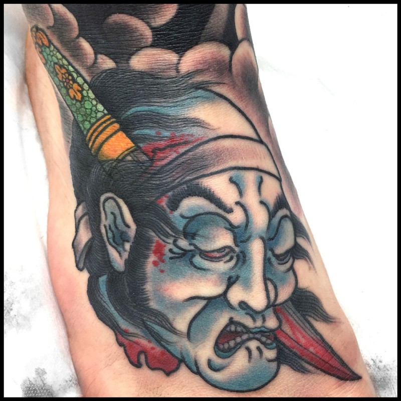 Asian traditional colored foot tattoo of severed man head with knife