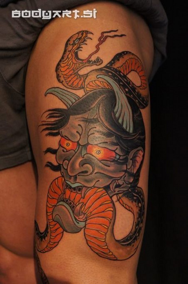 Asian traditional colored thigh tattoo of demonic face with snake