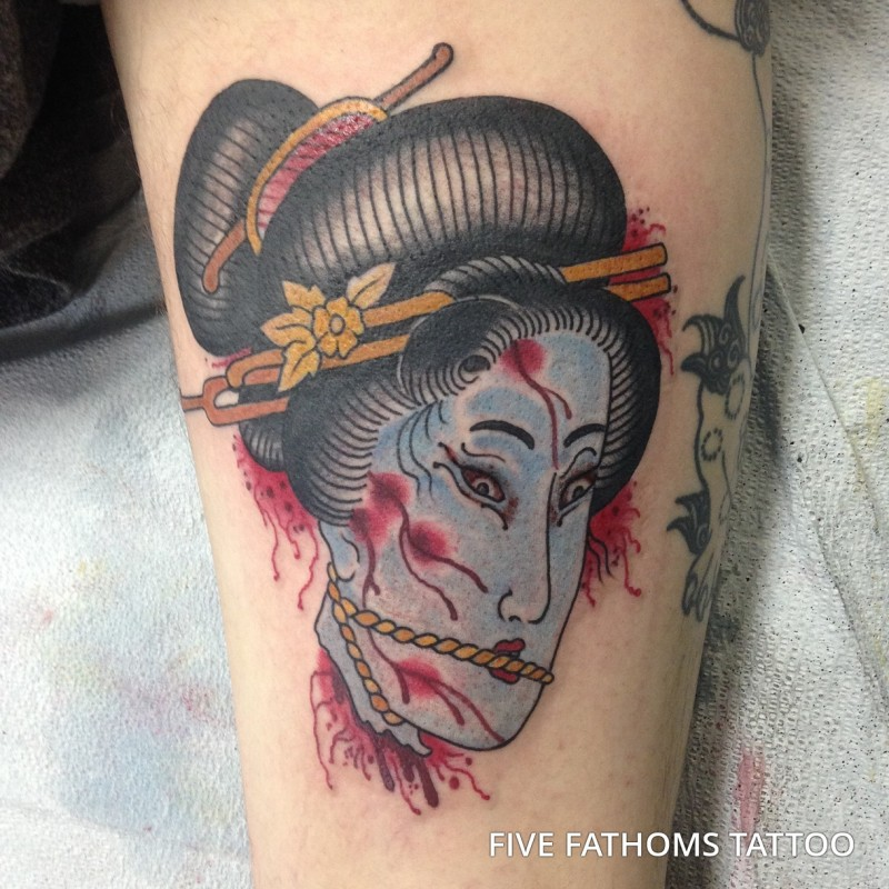 Asian traditional like colored severed woman`s head tattoo