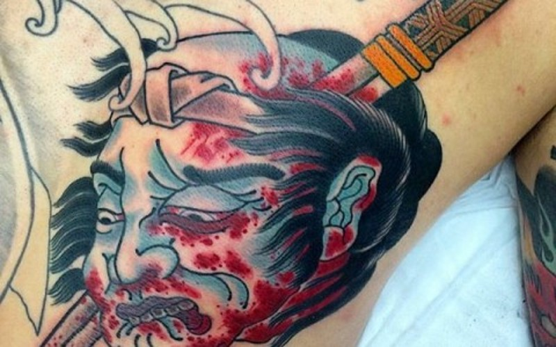 Asian traditional small colored bloody severed head tattoo with sword